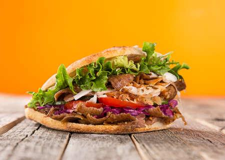 Turkish Doner Kebab Sandwich on wooden background.