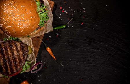 Tasty burgers on black stone table.