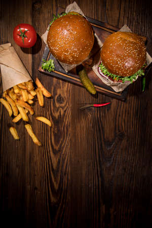 Tasty burgers on vintage wooden table, top view.