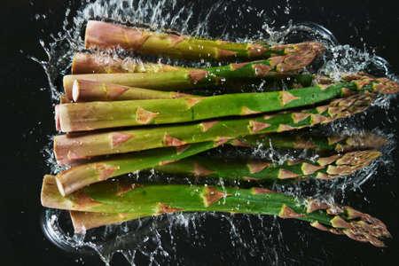 Falling fresh harvested asparagus, water splash during impact