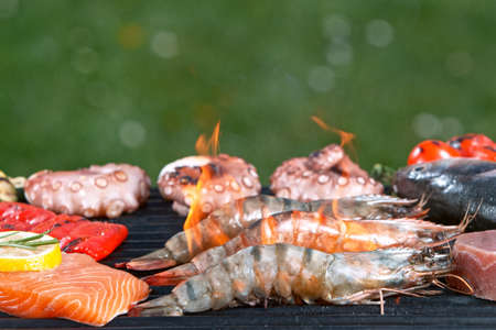 Assorted delicious grilled tiger shrimps with various meat and vegetables. Zdjęcie Seryjne