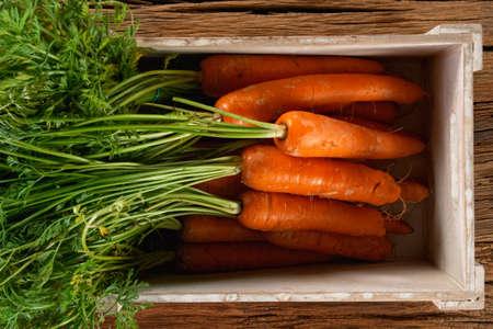 Fresh organic carrots in a wooden box.