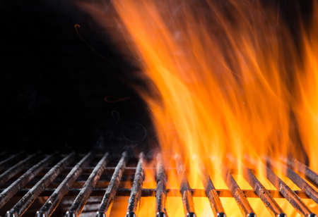 Empty flaming cast iron grate charcoal grill with open fire