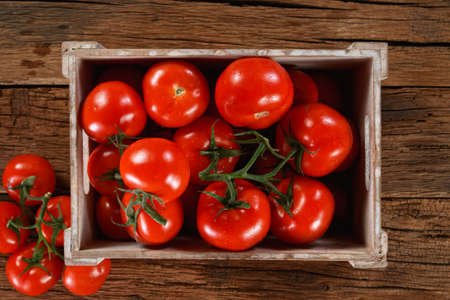 Fresh organic tomatoes in a wooden box.
