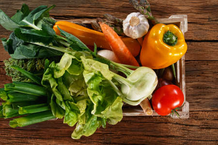 Fresh organic vegetables in a wooden box.