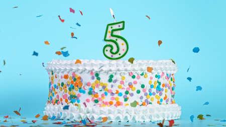 Colorful tasty birthday cake with candles shaped like the number 5. Archivio Fotografico