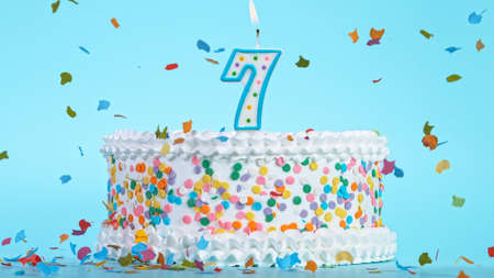 Colorful tasty birthday cake with candles shaped like the number 7. Archivio Fotografico