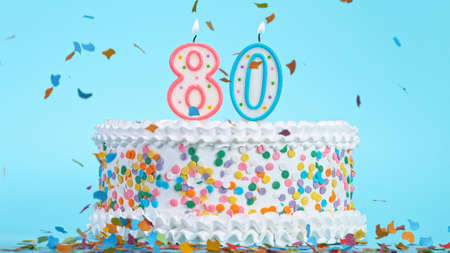 Colorful tasty birthday cake with candles shaped like the number 80.