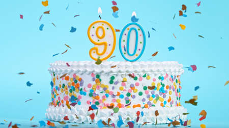 Colorful tasty birthday cake with candles shaped like the number 90.