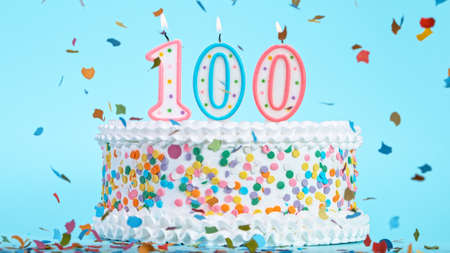 Colorful tasty birthday cake with candles shaped like the number 100. Pastel blue background.
