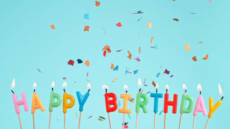 Colored confetti falling with happy birthday inscription on pastel blue background