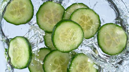 sliced cucumber with splashing water isolated on white background