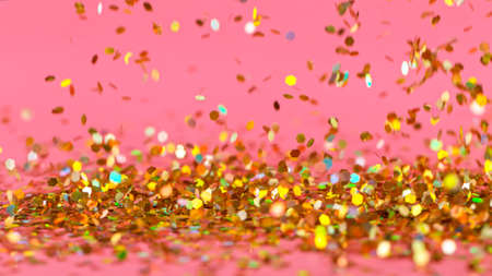 Golden glitter falling down on pink background.