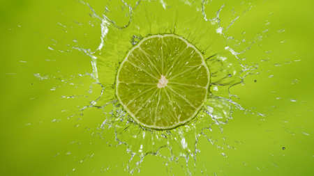 Fresh limes falling into water with splash