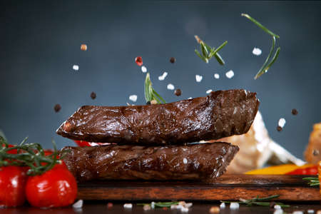 Delicious grilled beef steaks falling down on kitchen board