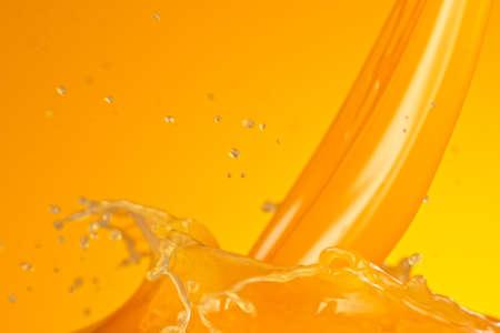 Pouring fresh orange juice splash