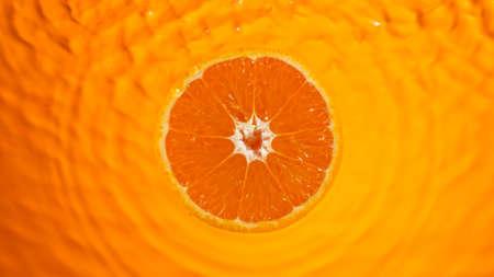 Fresh orange slice falling into splashing water splashing
