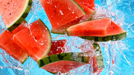Fresh pieces of water melon falling in water with splash