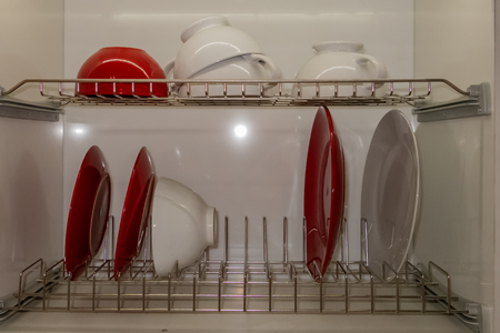 Vaisselle en porcelaine blanche séchée sur égouttoir en métal. Façon d'organiser la cuisine et de minimiser l'espace avec un égouttoir moderne dans l'armoire sur fond blanc.