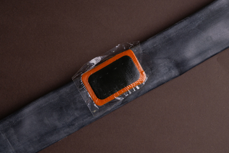 Patch on the camera of the bike. bicycle repair kit, wheels camera on wooden background