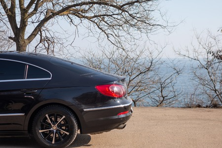 Fragment of a beautiful black car, standing on the beach. Stock Photo