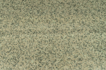 The structure of gray-beige granite. A natural stone. Industrial granite worktop in the restaurant