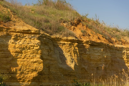 High sandy cliff overgrown with green grass and blue sky