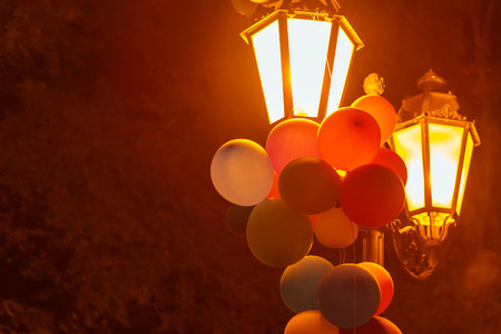 Multicolored balloons on a lantern in a night city park Imagens - 124887481