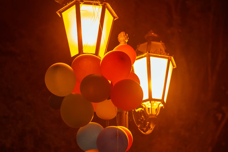 Multicolored balloons on a lantern in a night city park Imagens - 124887483