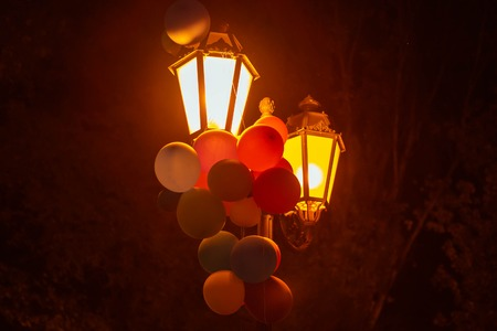 Multicolored balloons on a lantern in a night city park Imagens - 124887484