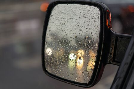 Raindrops on the rearview mirror of a car. In reflection, the headlights of other cars are out of focus Imagens
