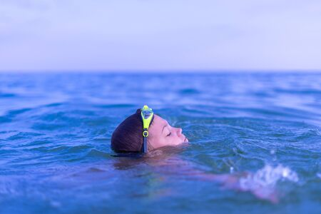 A 10-year-old boy swims in the sea at dawn with glasses for swimming