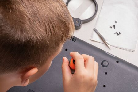A boy of 10 years old is sorting a laptop for cleaning and maintenance. Selective focus. Screwdrivers, purge cylinder, magnifying glass and spray cleaner in the frame.