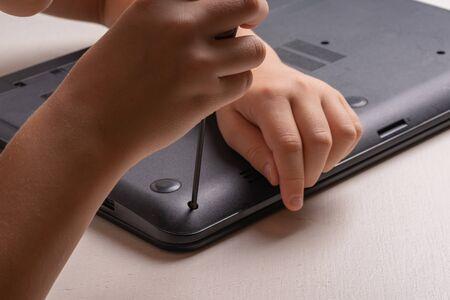 Un garçon de 10 ans trie un ordinateur portable pour le nettoyer et l'entretenir. Mise au point sélective. Tournevis, cylindre de purge, loupe et spray nettoyant dans le cadre Banque d'images
