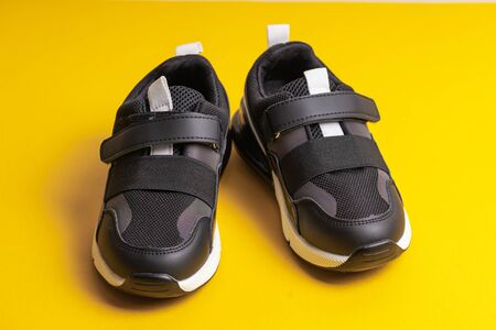 Black childrens school sneakers on a flypaper on a yellow background Stockfoto