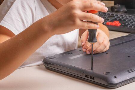 Un garçon de 10 ans trie un ordinateur portable pour le nettoyer et l'entretenir. Mise au point sélective. Tournevis, cylindre de purge, loupe et spray nettoyant dans le cadre