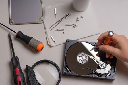 A teenager disassembles the hard drive of a computer to study its device