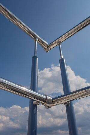 Stainless steel railing stairs from the outside of the building on a background of blue sky and beautiful clouds. Pipes, hinges, balusters made of stainless steel