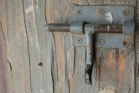 Old cracked paint on a gray wood panel. Creative vintage natural background. Old metal latch. Bolt Stock Photo