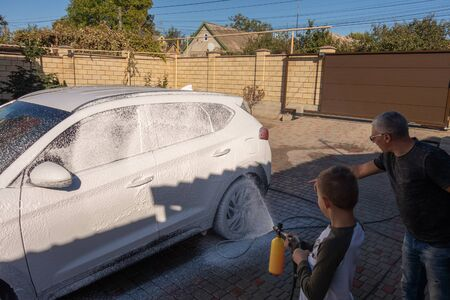 A middle-aged man teaches children of boys 4 and 10 years old to wash a car in the yard of his house on a summer sunny day. 2019.09.22. Odessa. Ukraine