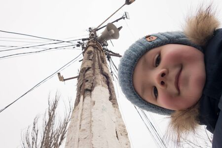 A little boy looks into the camera lens while shooting an old electric pylon