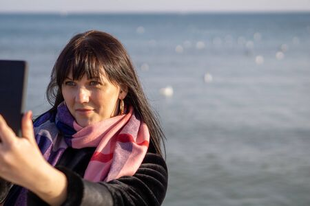 A young brunette woman in a black coat and pink scarf takes a picture of herself on the background of the sea on a sunny autumn day Standard-Bild - 134651215