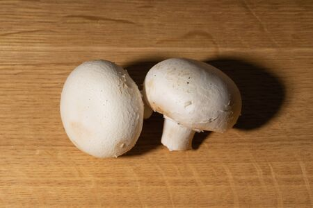 Several whole champignon mushrooms lie on a wooden table. Hard light and contrasting shadows