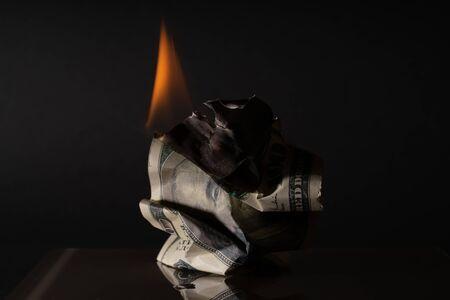 Burning hundred dollar bill. On a dark background. Creative vintage background