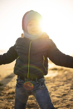 A 4 year old boy is playing and having fun on the seashore on a sunny winter day