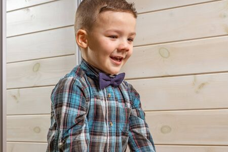 Laughing boy of 4 years old in a blue tart shirt on a light wooden background