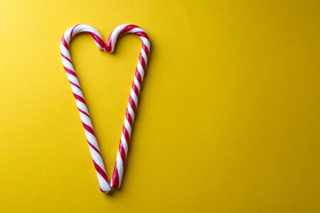 Peppermint candy canes on a yellow background. Stock Photo