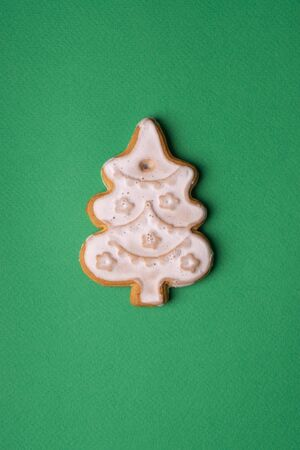 Handmade cookies in glaze in the form of Christmas toys on a green background