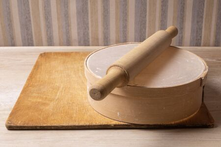 Plywood cutting board, wooden flour sieve and wooden rolling pin - tools for making dough