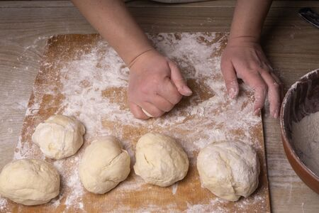 A woman kneads the dough. Plywood cutting board, wooden flour sieve and wooden rolling pin - tools for making dough